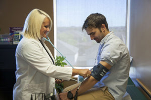 nurse detects hypertension using manual blood pressure cuff